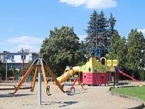 Yaslo, Pologne - 12 juillet 2018 : Terrain de jeu du ` s d'enfants en parc parmi la verdure Oscillations et bâtiments multicolore image libre de droits