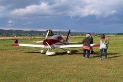 Yaslo, Polonia - 3 de julio de 2018: La familia en el aeropuerto está cerca de un avión biplaza ligero del turbopropulsor del col Fotos de archivo