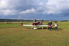 Yaslo, Polonia - 3 de julio de 2018: La familia en el aeropuerto está cerca de un avión biplaza ligero del turbopropulsor del col Fotografía de archivo libre de regalías