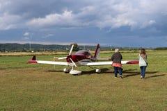 Yaslo, Polonia - 3 de julio de 2018: La familia en el aeropuerto está cerca de un avión biplaza ligero del turbopropulsor del col Foto de archivo