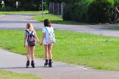 Yaslo, Polonia - 10 luglio 2018: Due ragazze che rollerblading tenersi per mano Stile di vita attivo Bambini sulle vacanze estive immagine stock libera da diritti