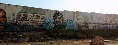 Israel-Palestine separation fence with mural. Yasser Arafat and Marwan Barghouti painted on Palestinian-Israeli separation wall at Qalandia checkpoint, between stock photography