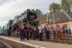 Yasynya, Ukraine - 29. September 2016: Musiker im Nationalkostüm, das gegen den Hintergrund der alten Dampflokomotive aufwirft Lizenzfreies Stockbild