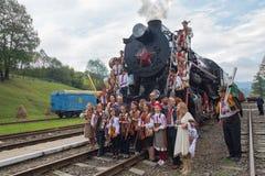 Yasynya, Ukraine - 29. September 2016: Musiker im Nationalkostüm, das gegen den Hintergrund der alten Dampflokomotive aufwirft Stockbilder