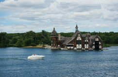 Yatch passing by beautiful house. Yatch on thousand islands Canada Royalty Free Stock Image