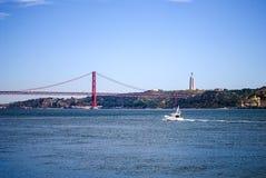 Yatch som går till 25th av April Bridge royaltyfria foton