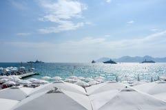 Yatchs和伞在一个海滩在戛纳,在法国南部 免版税库存图片