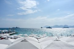 Yatchs och paraplyer på en strand i Cannes, söder av Frankrike royaltyfri bild
