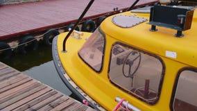 Yate amarillo amarrado al embarcadero en el estacionamiento almacen de video