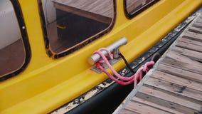 Yate amarillo amarrado al embarcadero en el estacionamiento metrajes