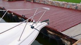 Yate blanco amarrado al embarcadero en el estacionamiento metrajes