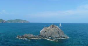 Yate blanco, catamarán, navegando en el mar, cerca del alto acantilado y de la isla metrajes