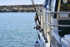 Yate blanco del motor en la expectativa de los turistas y de los pescadores en el embarcadero Barras de pesca con cebo de cuchara fotos de archivo libres de regalías