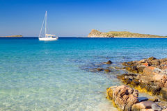 Yate blanco en la laguna idílica de la playa de Creta Foto de archivo libre de regalías