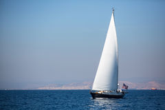 Yate de la navegación con las velas blancas en la niebla en el mar cerca del lujo de la costa Fotos de archivo libres de regalías