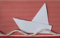 Yate de papel en el mar rayado rojo fotos de archivo libres de regalías