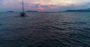 Yate solo, navegación del catamarán en el mar en la puesta del sol que va al sol almacen de video