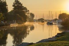 Yates amarrados en el río en mañana brumosa Fotografía de archivo