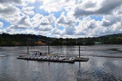 Yates en el cielo azul, nubes blancas en el agua en un día soleado Foto de archivo