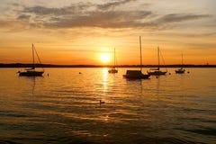 Yates que derivan en el lago durante puesta del sol hermosa del verano Imagenes de archivo
