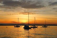 Yates que derivan en el lago durante puesta del sol hermosa del verano Foto de archivo