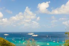 Yates y barcos de cruceros anclados en una bahía idílica en el Caribe Foto de archivo libre de regalías