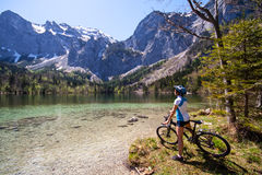 Yaung woman riding a bike beside Alpine lake Stock Photos