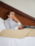 Yawing business woman laying on bed in hotel room Stock Images