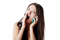 Yawing woman answering Stock Image