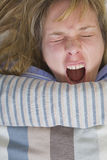 Yawn. Woman yawning in bed with a stripey duvet Stock Photos