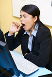 Yawn or pain?. A woman in her office was taken while she was yawning, but she also looks in pain Royalty Free Stock Photo
