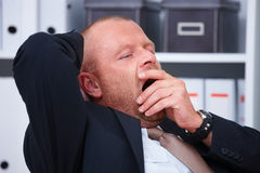Yawn - Tired businessman waiting to go home Stock Image