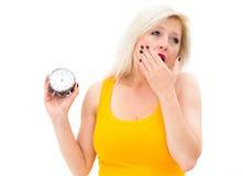 Yawn,young beautiful woman holding a clock Royalty Free Stock Photo