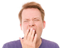 Yawn. Young man yawning - retouched and isolated on white background Royalty Free Stock Image