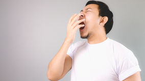 Yawning as it is very boring. An asian man with white t-shirt and grey background royalty free stock images