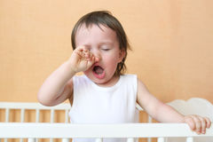 Yawning baby in white bed. Yawning baby age of 18 months in white bed Royalty Free Stock Photo