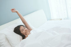 Yawning. Beautiful young Asian woman waking up in the morning. Royalty Free Stock Images