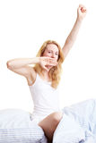 Yawning in bed. Happy blond woman sitting in her bed royalty free stock image