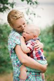 Yawning boy on mother's hands. Young mother kissing her yawning little son Stock Images