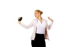 Yawning business woman holding alarm clock Stock Image