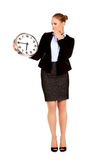Yawning business woman holding office clock Stock Photo