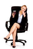 Yawning business woman sitting on wheel chair and holding cup of coffee Royalty Free Stock Photos