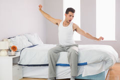 Yawning casual man sitting on bed stretching his arms Stock Photo