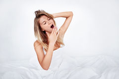 Yawning girl. Young girl yawning in bed Royalty Free Stock Photography