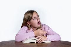 Yawning girl with book on white background. Yawning girl at the desk with a book learning on a white background Royalty Free Stock Images