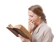 Yawning girl reading a boring book stock photos