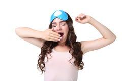 Yawning girl with sleeping mask. On white background stock photo
