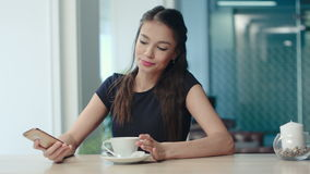 Yawning girl using her phone and drinking coffee in a cafe stock footage