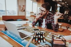 Yawning Graphic Designer Holds Measuring Tool. Portrait of Tired Sleepy Young Caucasian Freelancer Wearing Glasses Sits on Workplace with Ruler in Hand Looking stock image