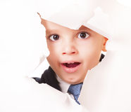 Yawning kid looks through a hole in white paper Royalty Free Stock Images